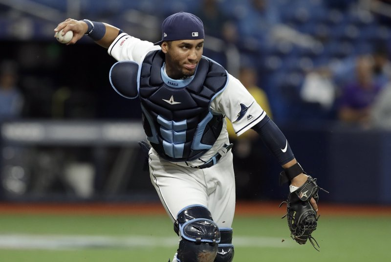 Tampa Bay Rays catcher Michael Perez fields a bunt by Colorado Rockies' Garrett Hampson during the third inning of a baseball game Monday, April 1, 2019, in St. (AP Photo/Chris O'Meara)
