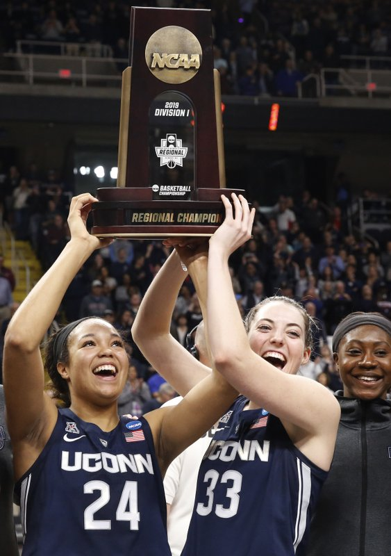 Connecticut forward Napheesa Collier (24) and guard Katie Lou Samuelson (33) hold up the trophy after defeating Louisville in a regional championship final in the NCAA women's college basketball tournament, Sunday, March 31, 2019, in Albany, N. (AP Photo/Kathy Willens)