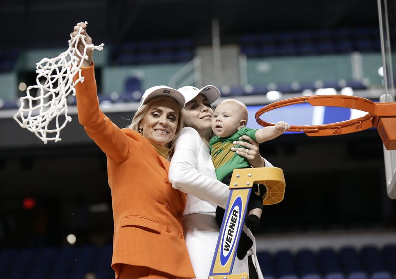 Baylor head coach Kim Mulkey, left, waves the net as she celebrates with her daughter Makenzie Fuller, center, and grandson Kannon Fuller, right, after Baylor defeated Iowa in a regional final women's college basketball game in the NCAA Tournament in Greensboro, N. (AP Photo/Gerry Broome)