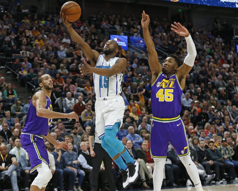 Charlotte Hornets guard Kemba Walker (15) lays up the ball as Utah Jazz's Rudy Gobert, left, and Donovan Mitchell (45) defend during the first half of an NBA basketball game, Monday, April 1, 2019, in Salt Lake City. (AP Photo/Rick Bowmer)