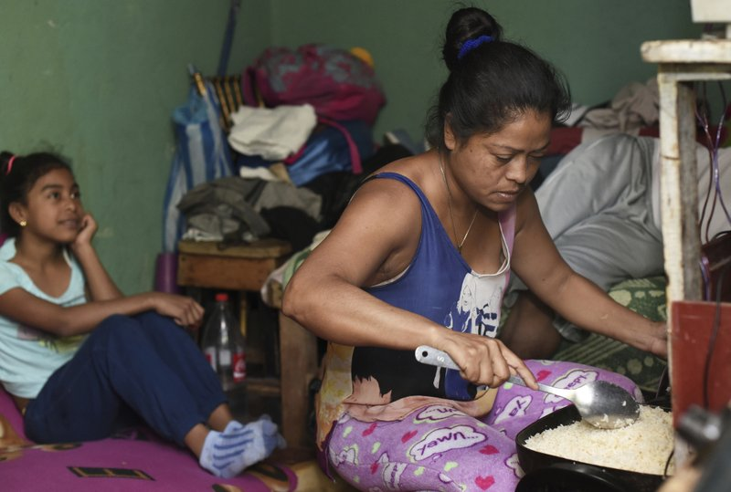 In this March 23, 2019 photo, Francia Leon cooks rice in her home in the La Carpio shantytown, on the outskirts of San Jose, Costa Rica. (AP Photo/Carlos Gonzalez)
