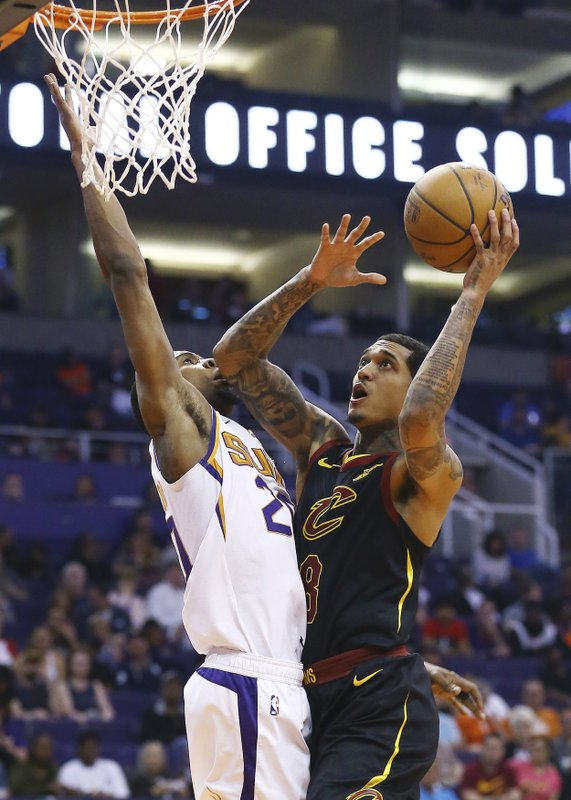 Cleveland Cavaliers guard Jordan Clarkson (8) drives to the basket against Phoenix Suns forward Josh Jackson, left, during the first half of an NBA basketball game Monday, April 1, 2019, in Phoenix. (AP Photo/Ross D. Franklin)