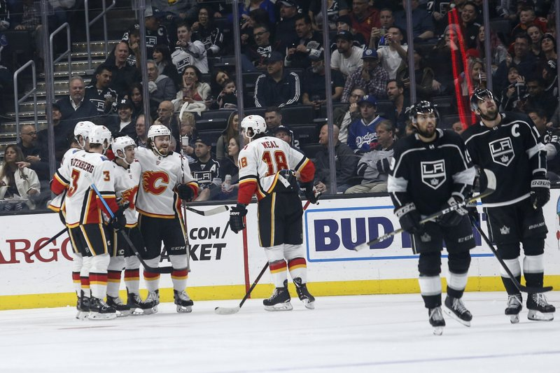 Calgary Flames players celebrate their goal against Los Angeles Kings during the second period of an NHL hockey game, Monday, April 1, 2019, in Los Angeles. (AP Photo/Ringo H.W. Chiu)