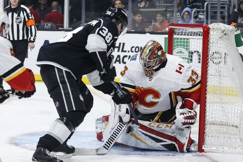 Calgary Flames goalie David Rittich (33) stops a shot by Los Angeles Kings forward Carl Grundstrom (38) during the second period of an NHL hockey game, Monday, April 1, 2019, in Los Angeles. (AP Photo/Ringo H.W. Chiu)