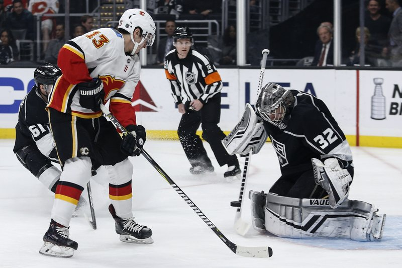 Los Angeles Kings goalie Jonathan Quick (32) blocks a shot by Calgary Flames forward Johnny Gaudreau (13) during the first period of an NHL hockey game Monday, April 1, 2019, in Los Angeles. (AP Photo/Ringo H.W. Chiu)