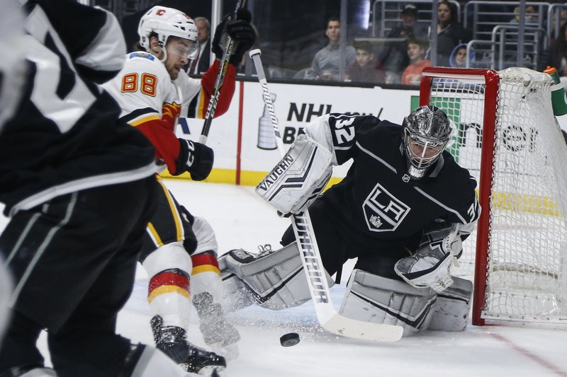 Los Angeles Kings goalie Jonathan Quick (32) stops a shot by Calgary Flames forward Andrew Mangiapane (88) during the first period of an NHL hockey game Monday, April 1, 2019, in Los Angeles. (AP Photo/Ringo H.W. Chiu)