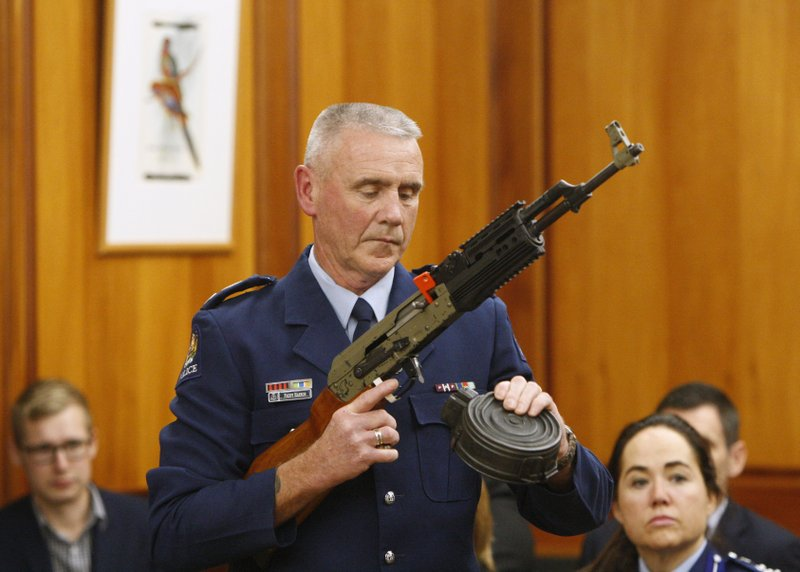 Police Sr. Sgt. Paddy Hannan shows New Zealand lawmakers a gun configuration that would be banned under new legislation in Wellington on April 2, 2019. (AP Photo/Nick Perry)