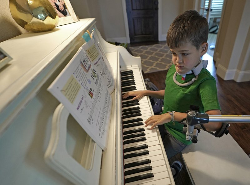 Braden Scott uses a device to support his left arm as he practices on the piano in Tomball, Texas on Friday, March 29, 2019. (AP Photo/David J. Phillip)