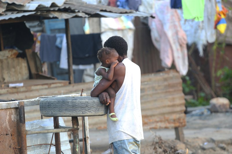 A father cuddles his daughter in Beira, Mozambique, Monday April 1, 2019. The death toll from the cyclone has reached over 500, as Mozambican and international health workers raced on Monday to contain the outbreak of cholera in the cyclone-hit city of Beira and surrounding areas, where cases of the disease has jumped to more than 1,000. (AP Photo/Tsvangirayi Mukwazhi)
