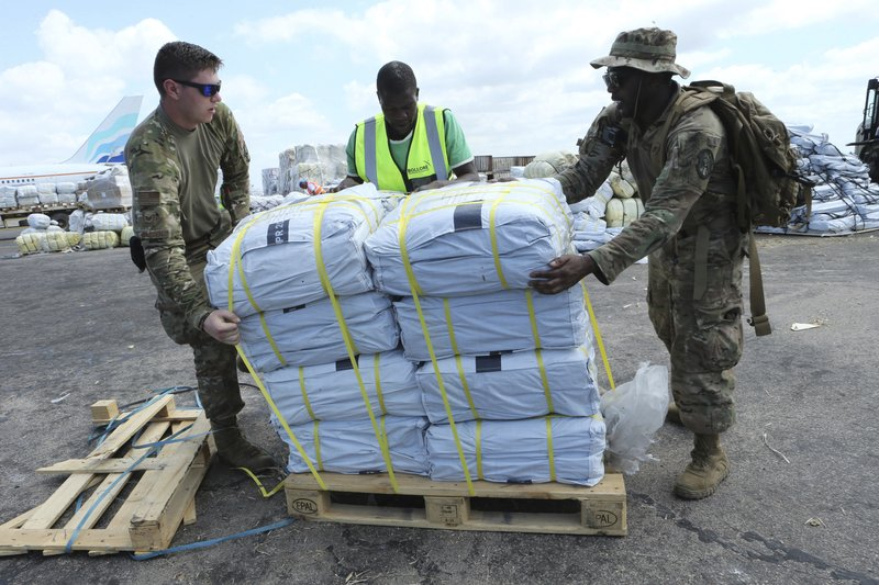 Members of the US army help load supplies at Beira International airport, Mozambique, Monday, April 1, 2019,  joining the humanitarian aid efforts following a cyclone that hit the country on March 14. (AP Photo/Tsvangirayi Mukwazhi)