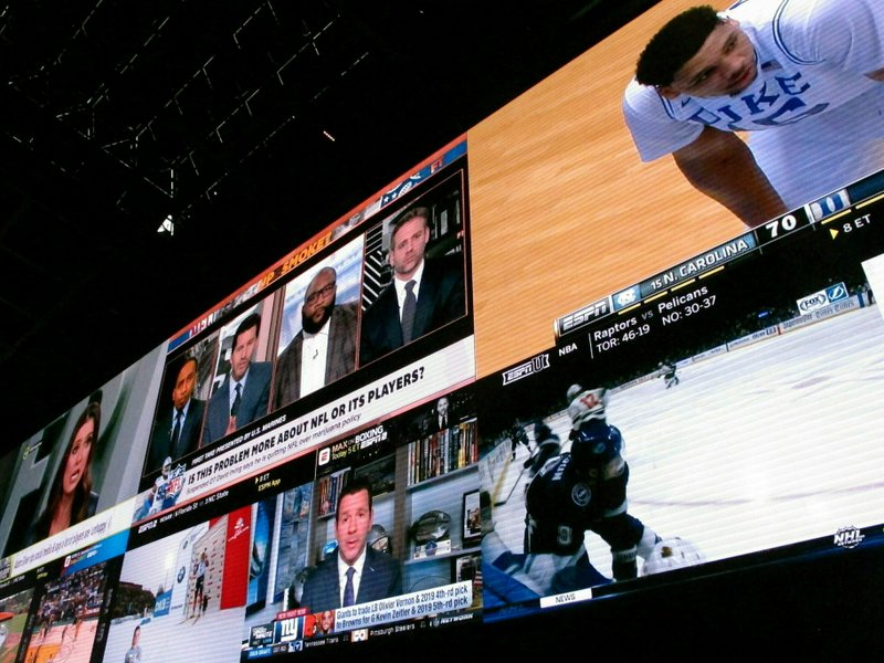 FILE - This March 8, 2019, file photo shows giants video screens inside the sports betting lounge at the Tropicana casino in Atlantic City N. (AP Photo/Wayne Parry, File)