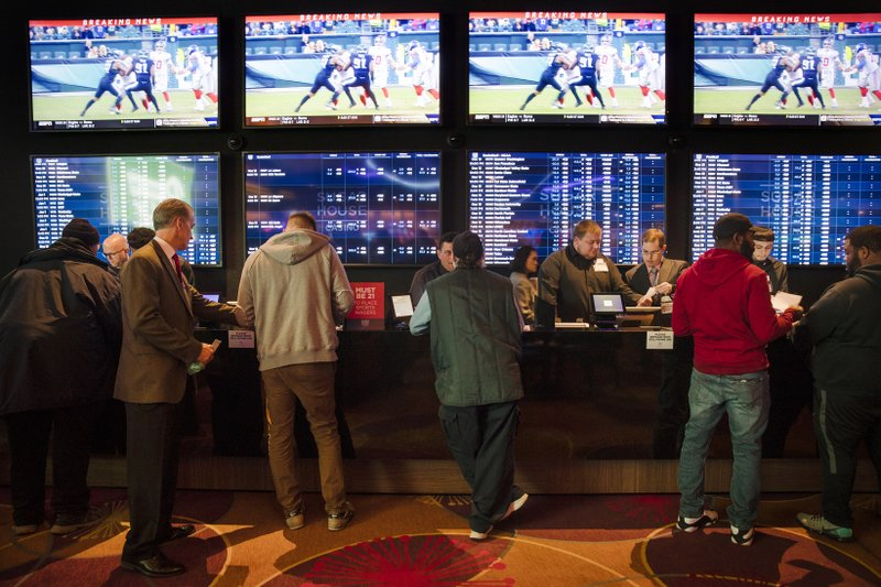 FILE - In this Dec. 13, 2018, file photo, gamblers place bets in the temporary sports betting area at the SugarHouse Casino in Philadelphia. (AP Photo/Matt Rourke, File)