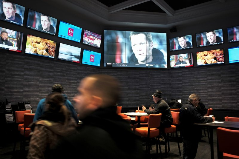 FILE - In this Jan. 28, 2019, file photo, patrons visit the sports betting area of Twin River Casino in Lincoln, R. (AP Photo/Steven Senne, File)