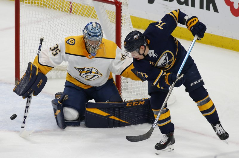 Buffalo Sabres forward Evan Rodrigues (71) passes the puck in front of Nashville Predators goalie Pekka Rinne (35) during the first period of an NHL hockey game Tuesday, April 2, 2019, in Buffalo, N. (AP Photo/Jeffrey T. Barnes)