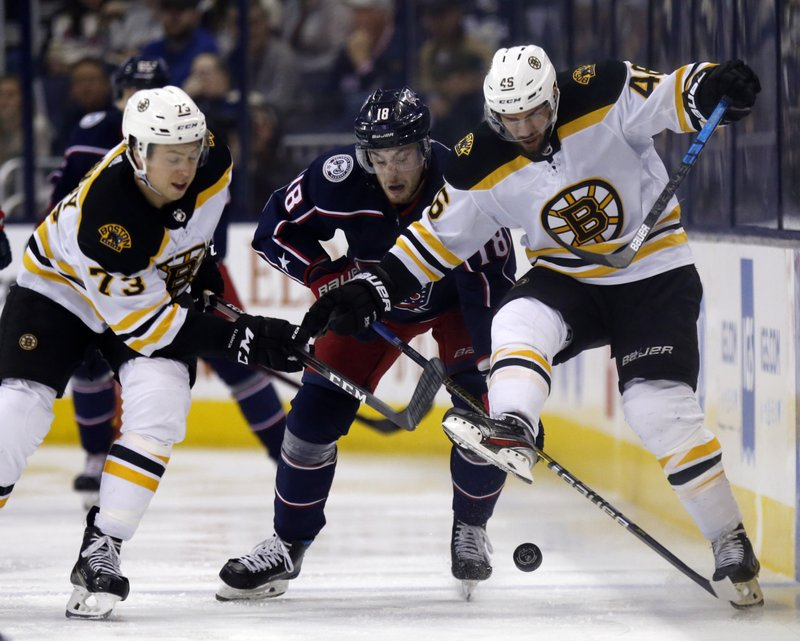 Columbus Blue Jackets forward Pierre-Luc Dubois, center, works against Boston Bruins defenseman Charlie McAvoy, left, and forward David Krejci, of the Czech Republic, during the second period of an NHL hockey game in Columbus, Ohio, Tuesday, April 2, 2019. (AP Photo/Paul Vernon)