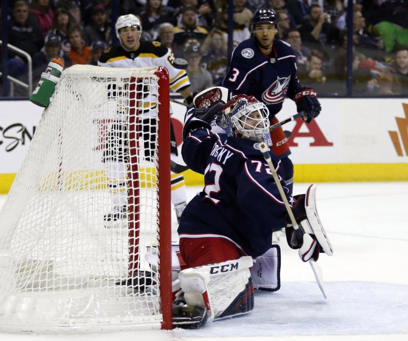 Columbus Blue Jackets goalie Sergei Bobrovsky, center, of Russia, watches the puck in front of Boston Bruins forward Brad Marchand, left, and Blue Jackets defenseman Seth Jones during the first period of an NHL hockey game in Columbus, Ohio, Tuesday, April 2, 2019. (AP Photo/Paul Vernon)