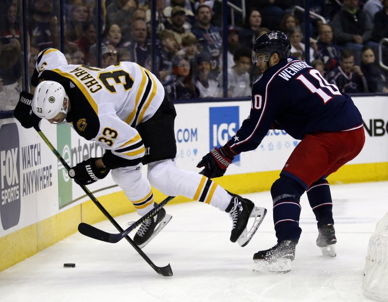 Columbus Blue Jackets forward Alexander Wennberg, right, of Sweden, trips Boston Bruins defenseman Zdeno Chara, of Slovakia, during the second period of an NHL hockey game in Columbus, Ohio, Tuesday, April 2, 2019. (AP Photo/Paul Vernon)