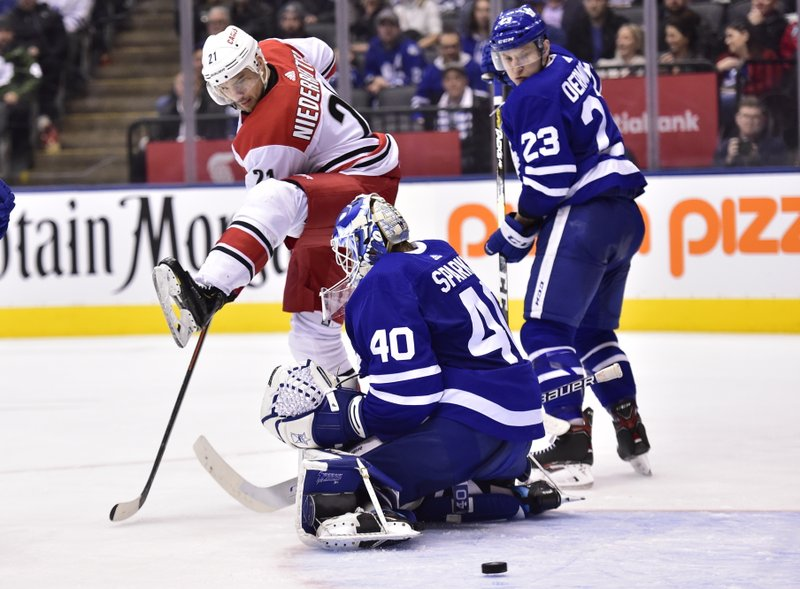 Carolina Hurricanes right wing Nino Niederreiter (21) looks to tip the puck past Toronto Maple Leafs goaltender Garret Sparks (40) as Toronto Maple Leafs' Travis Dermott (23) defends during the third period of an NHL hockey game, Tuesday, April 2, 2019, in Toronto. (Frank Gunn/The Canadian Press via AP)