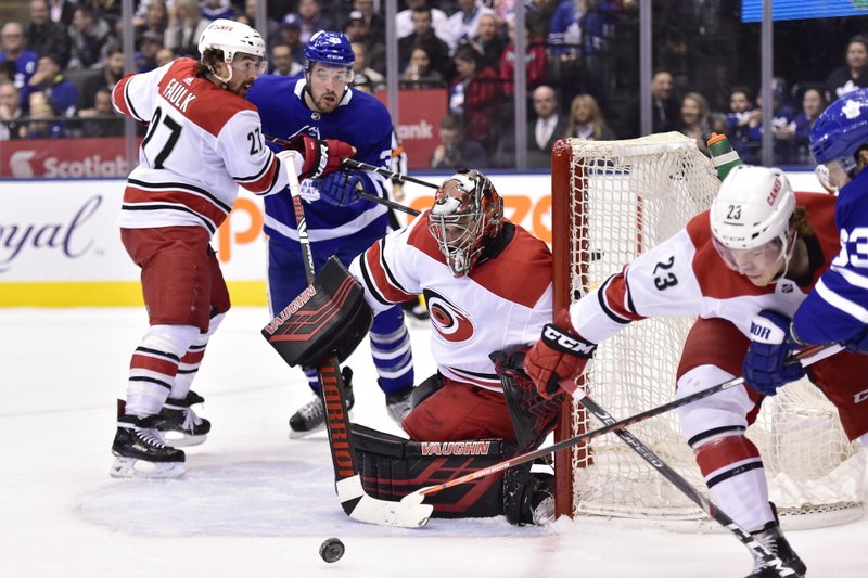 Carolina Hurricanes goaltender Petr Mrazek (34) covers the post as Carolina Hurricanes left wing Brock McGinn (23) and Toronto Maple Leafs left wing Tyler Ennis (63) battle during the second period of an NHL hockey game, Tuesday, April 2, 2019, in Toronto. (Frank Gunn/The Canadian Press via AP)