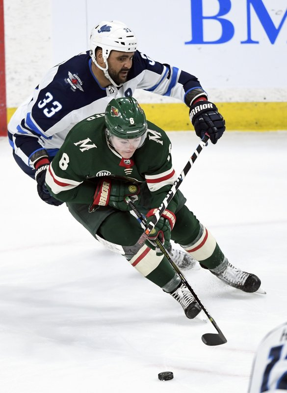 Minnesota Wild's Ryan Donato (6) has the puck against Winnipeg Jets' Dustin Byfuglien (33) during the third period of an NHL hockey game, Tuesday, April 2, 2019, in St. (AP Photo/Hannah Foslien)