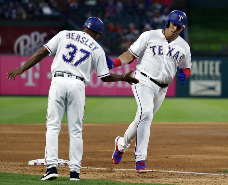 Texas Rangers third base coach Tony Beasley celebrates with Asdrubal Cabrera as he rounds the bag on his way home after hitting a two-run home run off a pitch from Houston Astros' Justin Verlander in the second inning of a baseball game in Arlington, Texas, Tuesday, April 2, 2019. (AP Photo/Tony Gutierrez)