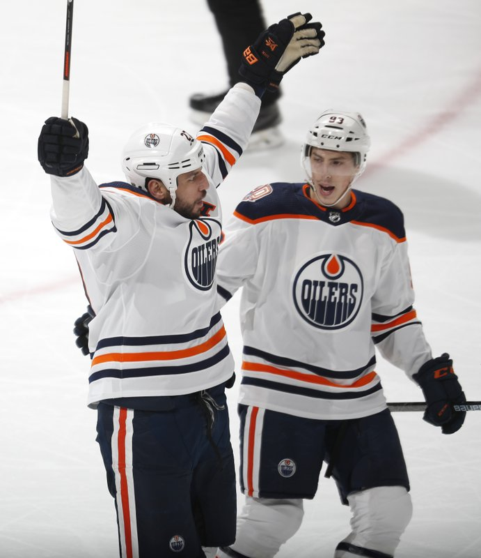 Edmonton Oilers left wing Milan Lucic, left, celebrates scoring a goal with Ryan Nugent-Hopkins in the first period of an NHL hockey game against the Colorado Avalanche Tuesday, April 2, 2019, in Denver. (AP Photo/David Zalubowski)