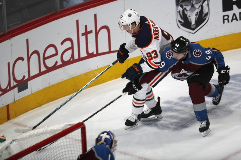 Edmonton Oilers center Ryan Nugent-Hopkins, left, tries to wrap around the net with the puck as Colorado Avalanche defenseman Samuel Girard covers in the first period of an NHL hockey game Tuesday, April 2, 2019, in Denver. (AP Photo/David Zalubowski)