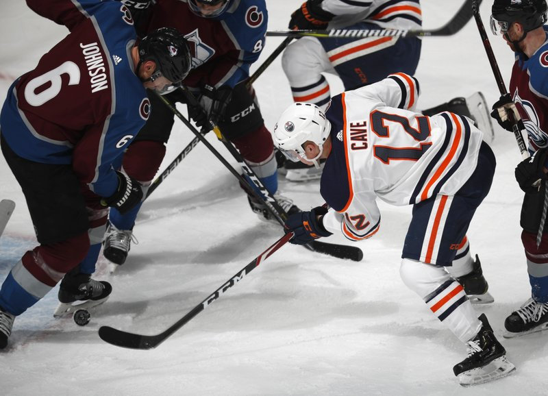 Colorado Avalanche defenseman Erik Johnson, left, stops a shot off the stick of Edmonton Oilers center Colby Cave in the first period of an NHL hockey game Tuesday, April 2, 2019, in Denver. (AP Photo/David Zalubowski)