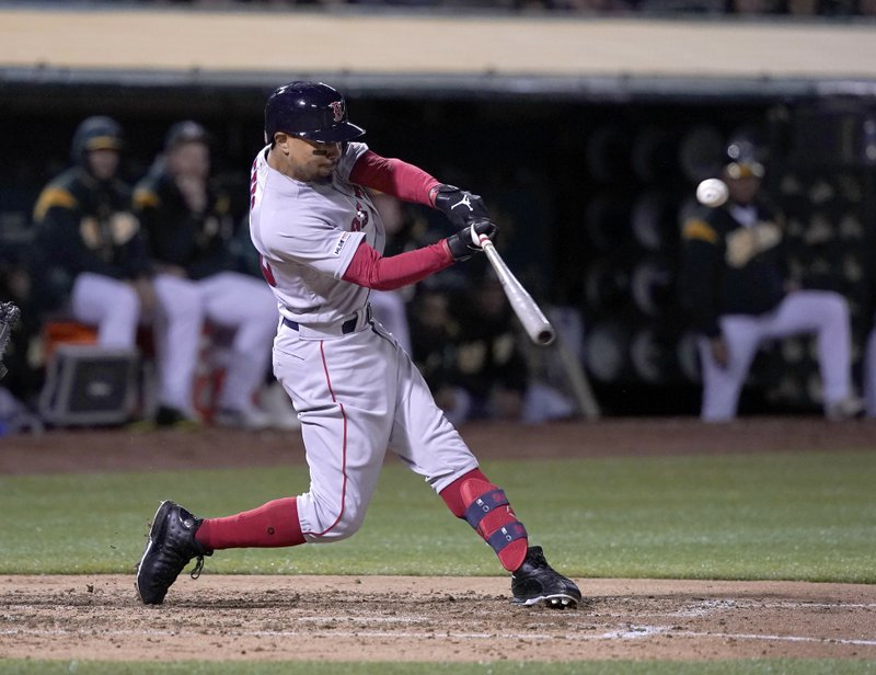 Boston Red Sox's Mookie Betts (50) hits a double against the Oakland Athletics during the third inning of a baseball game in Oakland, Calif. (AP Photo/Tony Avelar)