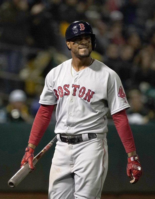 Boston Red Sox's Xander Bogaerts walks back to the dugout after striking out against the Oakland Athletics during the sixth inning of a baseball game in Oakland, Calif. (AP Photo/Tony Avelar)