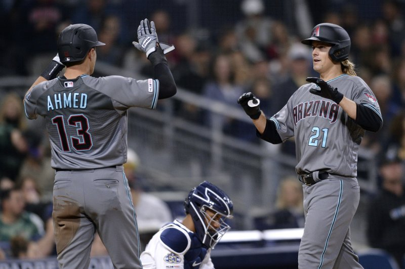 Arizona Diamondbacks' Zack Greinke (21) is congratulated by Nick Ahmed (13) after hitting a three-run home run during the fourth inning of a baseball game against the San Diego Padres, Tuesday, April 2, 2019, in San Diego. (AP Photo/Orlando Ramirez)