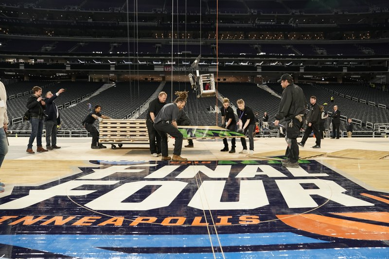 U.S. Bank Stadium operations crew installs the court for the NCAA Final Four college basketball tournament in Minneapolis, Friday, March 29, 2019. (Leila Navadi/Star Tribune via AP)