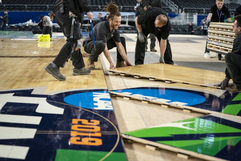 U.S. Bank Stadium operations worker Jaimyan Daveiga, center, helps install the court for the NCAA Final Four college basketball tournament in Minneapolis, Friday, March 29, 2019. (Leila Navadi/Star Tribune via AP)