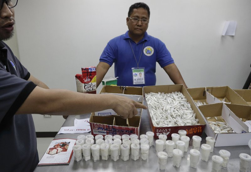 Staff of the Department of Environment and Natural Resources shows DNA sampling vials containing Tarantulas at their office in metropolitan Manila, Philippines on Wednesday, April 3, 2019. (about US$6,000), were seized by customs agents at Manila's airport last April 1. The endangered wildlife species were found concealed in gift-wrapped oatmeal and cookie boxes and was shipped from Poland. (AP Photo/Aaron Favila)