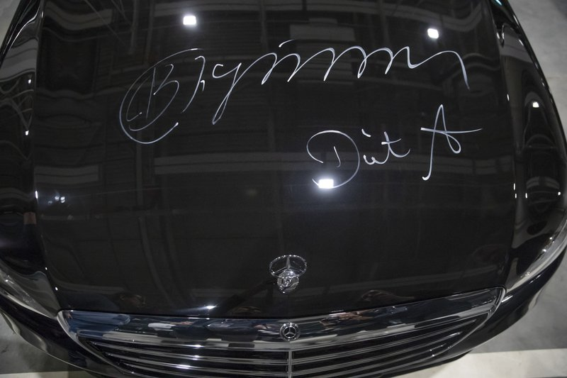 Autographs signed by Russian President Vladimir Putin's and Chairman of the Board of Management of Daimler AG Dieter Zetsche on the car hood, during an opening ceremony of the Mercedes Benz automobile assembly plant outside Moscow, Russia, Wednesday, April 3, 2019. ($281 million) investment it says will create 1,000 jobs.  (AP Photo/Pavel Golovkin, Pool)