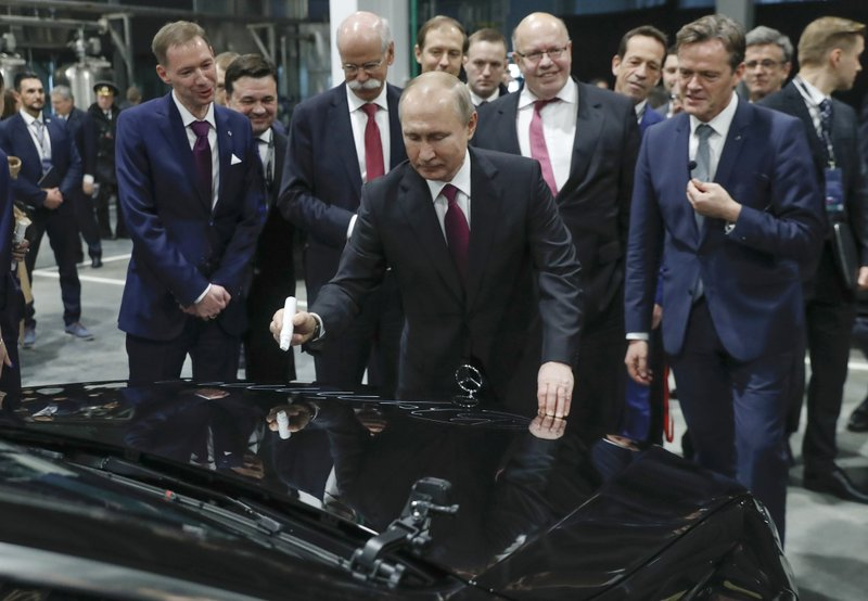 Russian President Vladimir Putin signs a car hood during an opening ceremony of the Mercedes Benz automobile assembly plant outside Moscow, Russia, Wednesday, April 3, 2019, with Chairman of the Board of Management of Daimler AG Dieter Zetsche, background centre left, and German economics ministers Peter Altmaier, centre right. ($281 million) investment it says will create 1,000 jobs.  (AP Photo/Pavel Golovkin, Pool)
