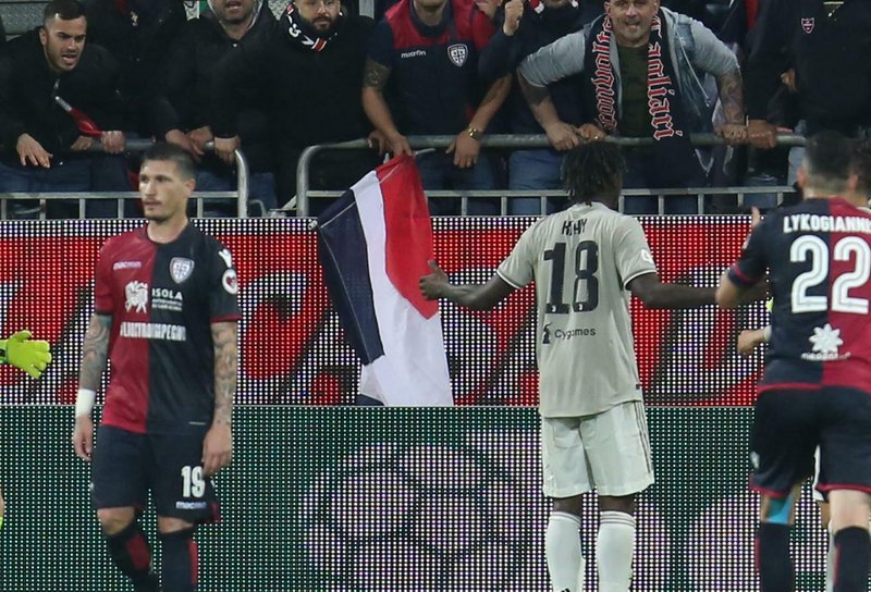 Cagliari fans shout to Juventus's Moise Kean, center with back to camera, after he scored his side's second goal during a Serie A soccer match between Cagliari and Juventus at the Sardegna Arena Stadium in Cagliari, Italy, Tuesday, April 2, 2019. (Fabio Murru/ANSA via AP)