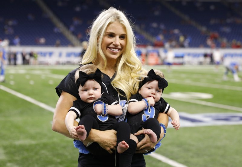 FILE - In this Sept. 24, 2017, file photo, Kelly Stafford, wife of Detroit Lions quarterback Matthew Stafford, holds the couple's twins Sawyer, left, and Chandler during pre-game of an NFL football game against the Atlanta Falcons, in Detroit. (AP Photo/Rick Osentoski, File)