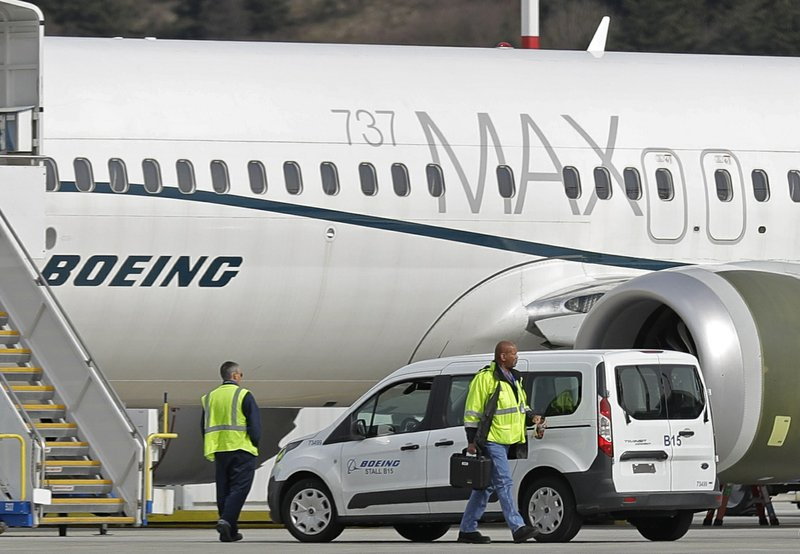 FILE - In this March 14, 2019, file photo, workers walk next to a Boeing 737 MAX 8 airplane parked at Boeing Field, in Seattle. (AP Photo/Ted S. Warren, File)