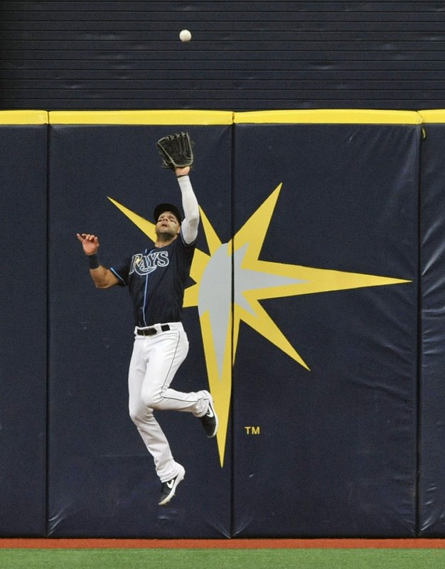 Tampa Bay Rays center fielder Kevin Kiermaier leaps to catch a fly ball hit by Colorado Rockies' David Dahl during the first inning of a baseball game Wednesday, April 3, 2019, in St. (AP Photo/Steve Nesius