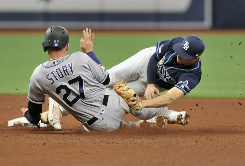 Tampa Bay Rays' Brandon Lowe, right, tags out Colorado Rockies' Trevor Story (27) at second base on a throw from Tampa Bay catcher Mike Zunino during the fourth inning of a baseball game Wednesday, April 3, 2019, in St. (AP Photo/Steve Nesius)