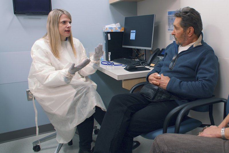 In this February 2019 photo provided by Brigham and Women's Hospital, Dr. Ann Woolley, an infectious disease specialist, speaks with patient Mark Natichinoi at the hospital in Boston. (Adam Knee/Brigham and Women's Hospital via AP)