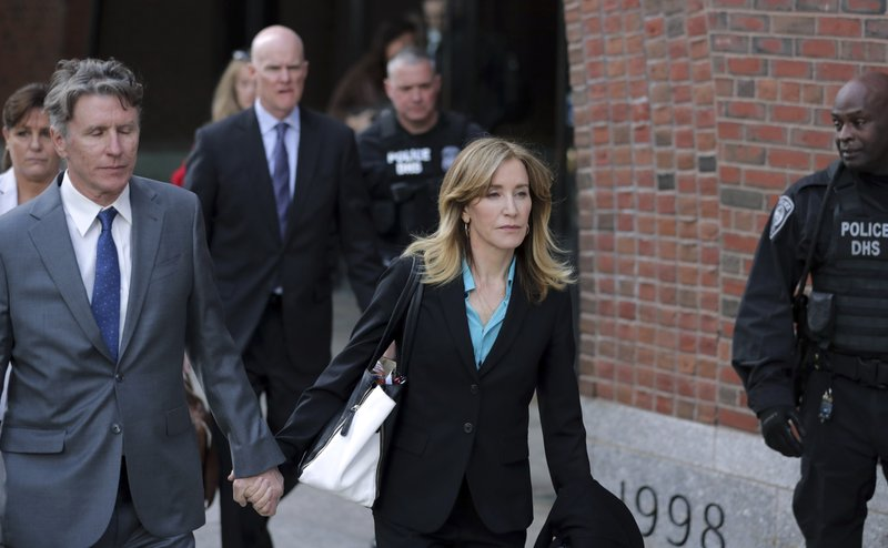 Actress Felicity Huffman departs federal court in Boston with her brother Moore Huffman Jr., left, on Wednesday, April 3, 2019, after facing charges in a nationwide college admissions bribery scandal. (AP Photos/Charles Krupa)
