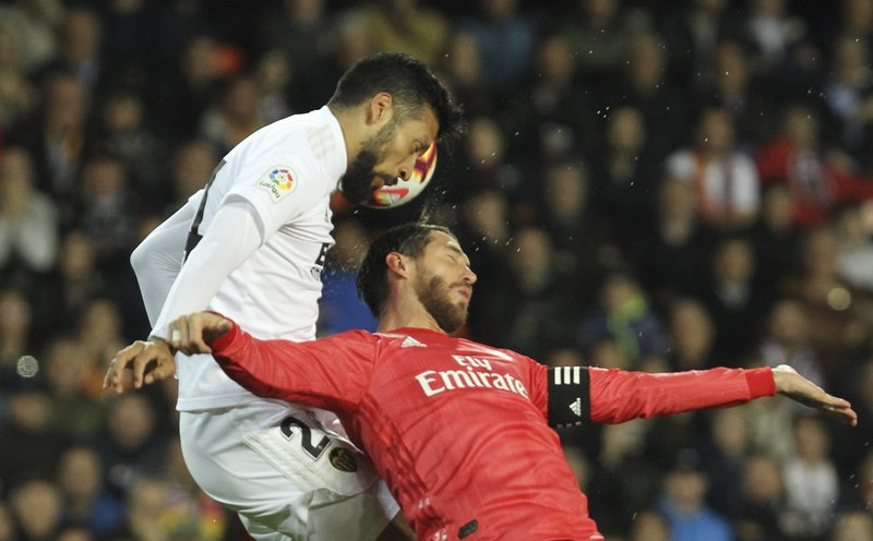 Real Madrid's defender Sergio Ramos, right, heads for the ball with Valencia's Ezequiel Garay during the Spanish La Liga soccer match between Valencia and Real Madrid at the Mestalla Stadium in Valencia, Spain, Wednesday, April 3, 2019. (AP Photo/Alberto Saiz)