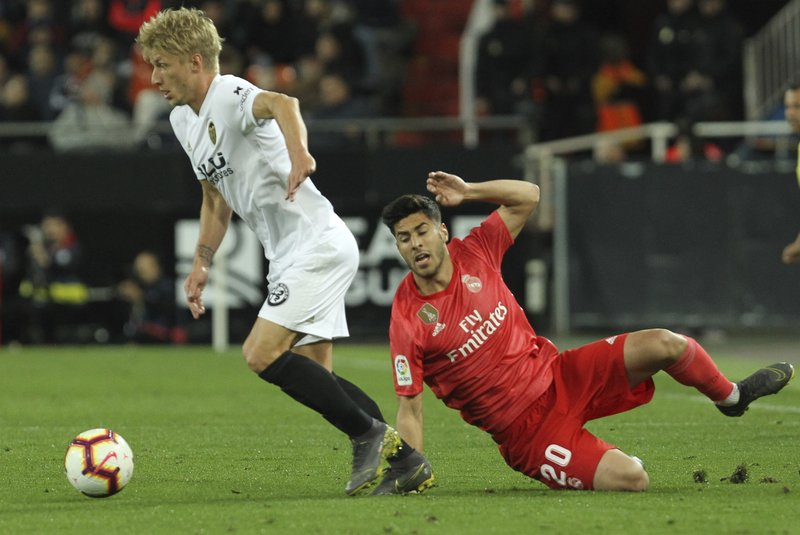 Valencia's Daniel Wass, left, vies for the ball with Real Madrid's midfielder Marco Asensio during the Spanish La Liga soccer match between Valencia and Real Madrid at the Mestalla Stadium in Valencia, Spain, Wednesday, April 3, 2019. (AP Photo/Alberto Saiz)