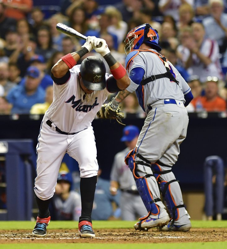 Miami Marlins' Starlin Castro prepares to pound his bat against the ground after striking out, as New York Mets' Tomas Nido (3) walks back to the dugout at the end of the sixth inning of a baseball game Wednesday, April 3, 2019, in Miami. (AP Photo/Jim Rassol)