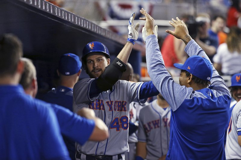 New York Mets pitcher Jacob deGrom (48) is congratulated by teammates after hitting a solo home run against the Miami Marlins during the third inning of a baseball game in Miami, Wednesday, April 3, 2019. (David Santiago/Miami Herald via AP)