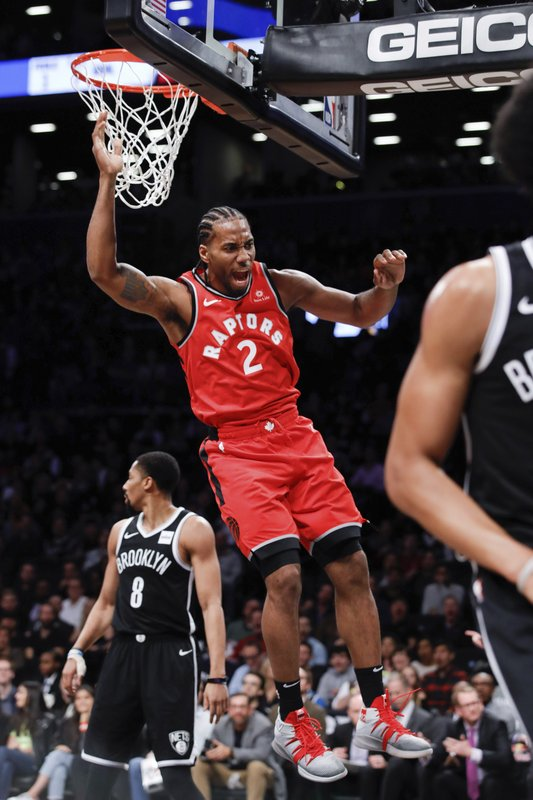 Toronto Raptors forward Kawhi Leonard comes down after a slam dunk during the first half of an NBA basketball game against the Brooklyn Nets, Wednesday, April 3, 2019, in New York. (AP Photo/Kevin Hagen)