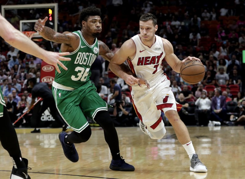 Miami Heat guard Goran Dragic (7) drives to the basket as Boston Celtics guard Marcus Smart defends during the first half of an NBA basketball game Wednesday, April 3, 2019, in Miami. (AP Photo/Lynne Sladky)