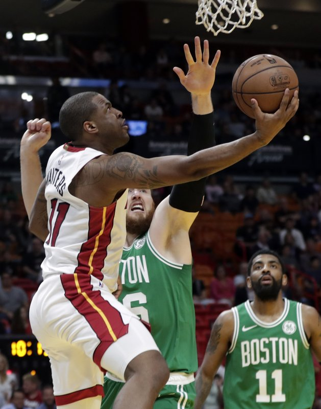 Miami Heat guard Dion Waiters (11) goes to the basket as Boston Celtics center Aron Baynes defends during the first half of an NBA basketball game Wednesday, April 3, 2019, in Miami. (AP Photo/Lynne Sladky)